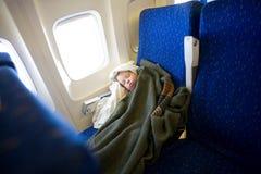 De slaap van het kind in vliegtuig Stock Fotografie