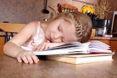De slaap van het meisje bij boeken Royalty-vrije Stock Afbeeldingen