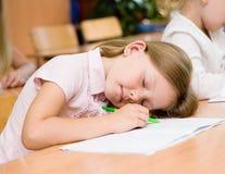 De slaap van het meisje in klaslokaal stock afbeelding