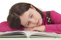 De slaap van het meisje op een open boek Royalty-vrije Stock Afbeeldingen
