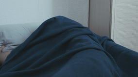 De slaap van de mens in bed het jongenskielzog omhoog van een nachtmerrie stock footage