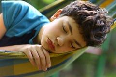 De slaap van de tienerjongen in hangmat stock foto