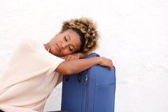 De slaap van de zwartereiziger met koffer op stoep Stock Foto