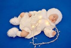 De slaapbaby in het kostuum van een Nieuwjaar van de Sneeuwvlok met de glanzende slinger in de vorm van hart op een blauwe achter Stock Afbeeldingen