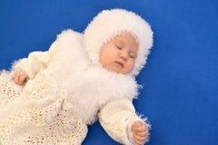 De slaapbaby in het kostuum van een Nieuwjaar van de Sneeuwvlok op een blauwe achtergrond Stock Foto's