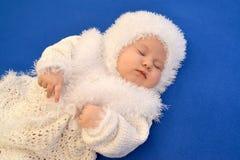 De slaapbaby in het kostuum van een Nieuwjaar van de Sneeuwvlok op een blauwe achtergrond Royalty-vrije Stock Foto's