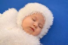 De slaapbaby in het kostuum van een Nieuwjaar van de Sneeuwvlok op een blauwe achtergrond Stock Fotografie