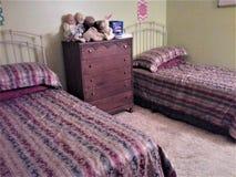 De slaapkamer van kinderen met twee bedden, opmaker en speelgoed royalty-vrije stock afbeeldingen