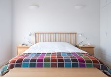 De slaapkamerbinnenland van de Scandistijl met houten slaapkamermeubilair, witte geschilderde muren, wit beddegoed en kleurrijke  royalty-vrije stock foto's