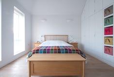 De slaapkamerbinnenland van de Scandistijl met houten slaapkamermeubilair, witte geschilderde muren, wit beddegoed en kleurrijke  stock fotografie