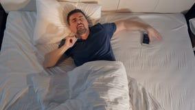 De slaapman die de tijd controleren op smartphone 4K stock footage