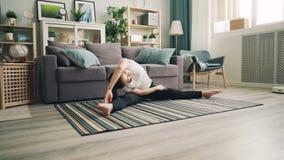 De slanke Aziatische meisjes vrouwelijke student doet yoga thuis van genietend uitrekt oefeningen zittend op vloer op tapijt en stock videobeelden