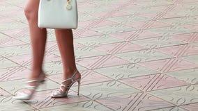 De slanke benen van vrouwen in schoenen, die op een de zomerdag van de bestratingsplak lopen met witte leerzak stock videobeelden