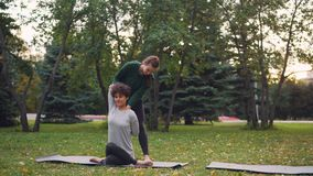 De slanke instructeur van de meisjesyoga helpt haar student om Gomukhasana tijdens individuele praktijk in park in de herfst te l stock videobeelden