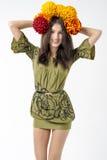 De slanke jonge donkerbruine vrouw in een kleding met een boeket van de herfst bloeit op haar hoofd Stock Foto's