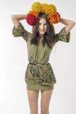 De slanke jonge donkerbruine vrouw in een kleding met een boeket van de herfst bloeit op haar hoofd Royalty-vrije Stock Afbeelding