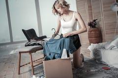 De slanke jonge kleren van de vrouwenverpakking van ex vriend in dozen stock afbeeldingen