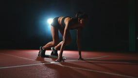 De slanke jonge meisjesatleet is in positie beginnen in de stootkussens op het spoor in langzame motie te lopen stock videobeelden