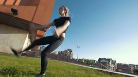 De slanke jonge vrouw voert acrobatische sprong op het gras op achtergrondcityscape uit stock video