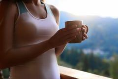 De slanke Kaukasische vrouw houdt kop thee in haar handen bij bergtoevlucht Sportenmeisje met hete koffiemok bij houten balkon Royalty-vrije Stock Foto's