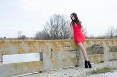De slanke rode kleding van de vrouwenslijtage plotseling en hoge hielen Stock Foto