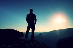 De slanke toerist op scherpe piek van rotsachtige berg let op over nevelige en mistige ochtendvallei aan Zon stock foto's