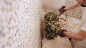De slanke vrouw in bad krijgt het stomen van massage met hete eiken bladerenbezems, in stoom-ruimte stock footage