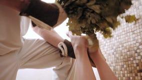 De slanke vrouw in bad krijgt het stomen van massage met hete eiken bladerenbezems, in stoom-ruimte stock video