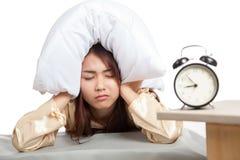 De slaperige Aziatische oren van de het hoofdkussendekking van het meisjesgebruik en wekker Stock Fotografie