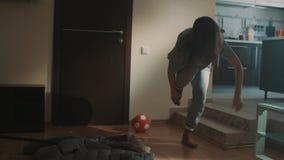 De slaperige de meisjesgeeuwen en struikelingen op gevallen rek in woonkamer krijgen boze schoppen het stock videobeelden