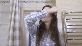 De slaperige gewekte vrouw in glazen kamt haar haar in de badkamers stock footage
