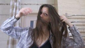 De slaperige gewekte vrouw in glazen kamt haar haar met handen en geeuw in de badkamers stock videobeelden