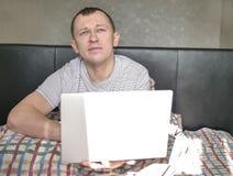 De slaperige jonge mens zit in bed, houdt laptop royalty-vrije stock fotografie