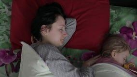 De slaperige jonge vrouw met haar baby wil niet in de ochtend ontwaken stock videobeelden