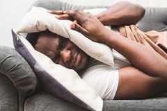 De slaperige kerelontwaken vroeg na het horen van wekkersignaal en willen niet opstaan royalty-vrije stock foto
