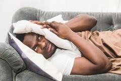 De slaperige kerelontwaken vroeg na het horen van wekkersignaal en willen niet opstaan stock foto's