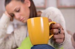De slaperige kop van de vrouwenholding van koffie royalty-vrije stock foto