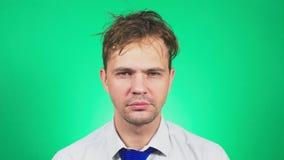 De slaperige, slordige jonge mens in een kostuum en de band, geeuwen en onderzoeken de camera 4k, groene achtergrond, langzame mo stock video
