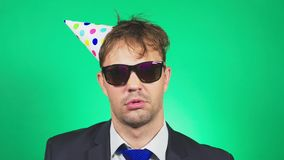 De slaperige, slordige jonge mens in een kostuum en de band, met een kater, in een feestelijk GLB, geeuwen en bekijken de camera  stock video