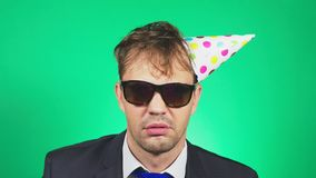 De slaperige, slordige jonge mens in een kostuum en de band, met een kater, in een feestelijk GLB, geeuwen en bekijken de camera  stock videobeelden
