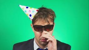 De slaperige, slordige jonge mens in een kostuum en de band, met een kater, in een feestelijk GLB, geeuwen en bekijken de camera  stock footage