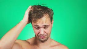 De slaperige, slordige jonge mens met een naakt torso, geeuwen en onderzoekt de camera 4k, groene achtergrond, langzame motie stock video