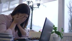 De slaperige uitgeputte vermoeide studentenvrouw gebruikt moderne computertechnologie aan het voorbereidingen treffen voor examen stock video