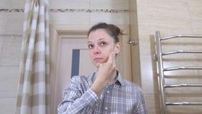 De slaperige vrouw in glazen in de badkamers veegt het gezicht met een lotion met een katoenen stootkussen af stock video