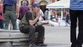 De slechte dakloze mens eet van plastic plaatzitting op de straat stock video