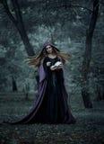 De slechte heks in een lange donkere mantel, giet een werktijd Stock Foto