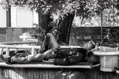 De slechte hongerige en vermoeide dakloze ex militaire de militairslaap van de veteraanmens in de schaduw op de bank in stedelijk royalty-vrije stock foto's