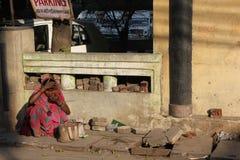 De slechte Indische vrouw zit op een geruïneerde straat Royalty-vrije Stock Foto
