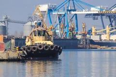 De sleepboot is bij de pijler in de zeehaven De haven van de lading royalty-vrije stock afbeelding