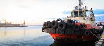 De sleepboot is bij de pijler in de zeehaven stock fotografie